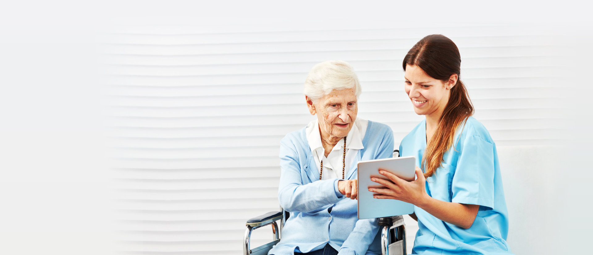 nurse and senior woman in the wheelchair are looking at the tablet devices