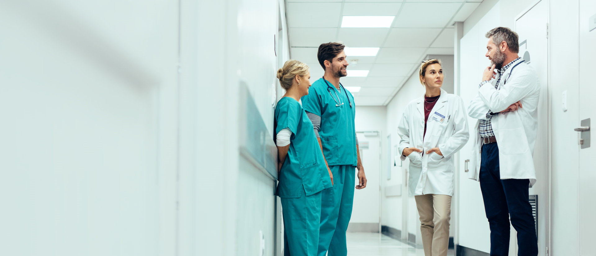 group of medical staff are having a conversation at the hallway of the hospital